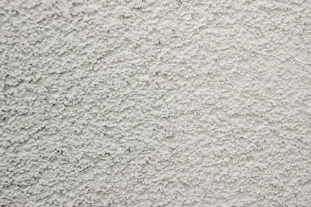white lime plaster texture wall of a building, wallpaper backdrop , space for text