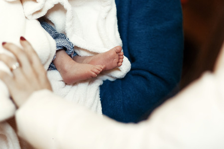 baby baptism. cute feet of a little boy at christening ceremony in church in godfather hands