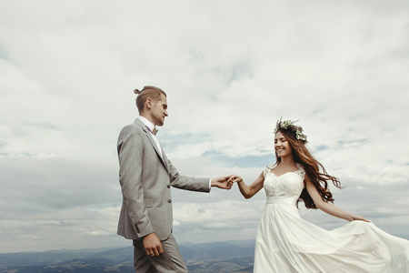 gorgeous bride and groom holding hands and dancing at sky and clouds, moment of true happiness, luxury ceremony at mountains with amazing view, space for text