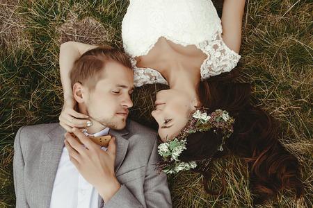prachtige bruid en stijlvolle bruidegom liggend op de top, close-up, boho bruidspaar, luxe ceremonie op bergen