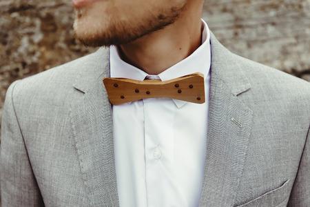 stylish grooms wooden bow tie, close up on background rocks at mountains, luxury boho wedding Stock Photo