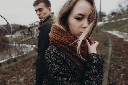 スタイリッシュな流行に敏感なカップルが公園の背景にポーズします。本文スペースと官能的な大気の瞬間。ファッショナブルな男と女の感情を示