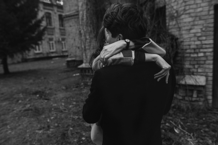 stylish couple having fun and hugging in autumn park. hands closeup. man and woman . joyful moments of true happiness. family togetherness concept.  atmospheric emotions. black white photo