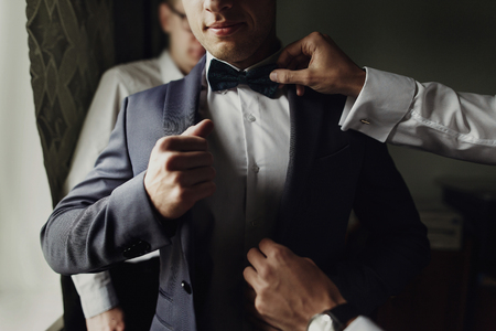 Des groomsmen élégants qui aident le bon groom à se préparer le matin pour la cérémonie de mariage. homme de luxe en costume dans la chambre. espace pour le texte. Jour de mariage. Banque d'images