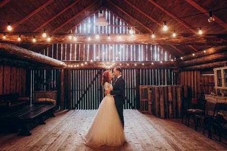 stijlvolle bruidegom en gelukkige bruid knuffelen onder retro lampen lichten in houten schuur. rustiek huwelijksconcept, ruimte voor tekst. jonggehuwden paar omarmen, sensuele romantisch moment