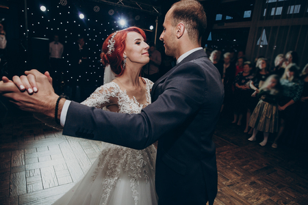 happy bride and stylish groom dancing at wedding reception. gorgeous wedding couple performing their first dance in restaurant. newlyweds, happy emotional moment. space for text Foto de archivo