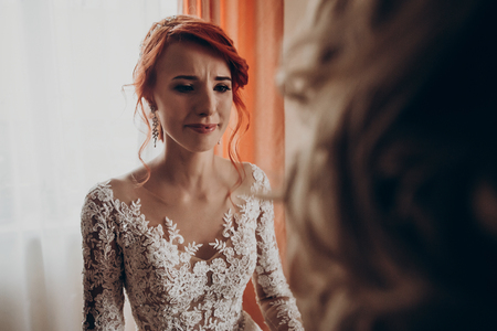 stylish happy bride crying looking at mother or grandmother, family values. emotional moment.  wedding morning preparation. bridal getting ready. space for text. mother of the bride