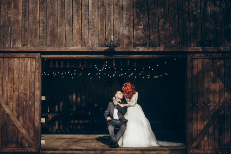 rustic wedding couple posing and hugging at background of wooden barn with retro lights, space for text. happy stylish bride and groom at wood wall in country, bohemian newlyweds 免版税图像 - 76560296
