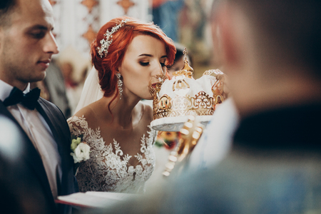happy bride and stylish groom kissing crowns and baptizing during wedding ceremony. wedding couple at matrimony in church. emotional moment, space for text. religion unity concept Stock Photo