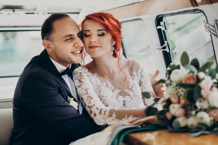 stylish happy bride and groom embracing, gently hugging in retro car and smiling. emotional moment, space for text. luxury wedding newlyweds couple, honeymoon travel
