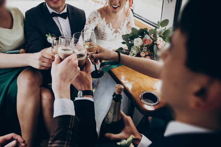 hands with glasses of champagne clinking, stylish happy bride and groom toasting laughing and having fun with bridesmaids and groomsmen inside car. emotional moment, space for text. wedding party Stock Photo