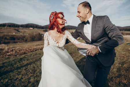 rustic wedding couple running and having fun in mountains in sunset light. space for text. happy stylish bride and groom laughing, true feelings. emotional romantic moment. space for text