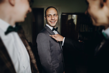 stylish groom laughing and having fun with groomsmen while getting ready in the morning for wedding ceremony. luxury man in suit with his friends smiling in room. space for text. Stock Photo - 76560572