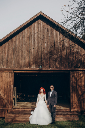 rustic wedding couple posing and standing at background of wooden barn. wedding concept, space for text. happy stylish bride and groom at wood wall in country, bohemian newlyweds