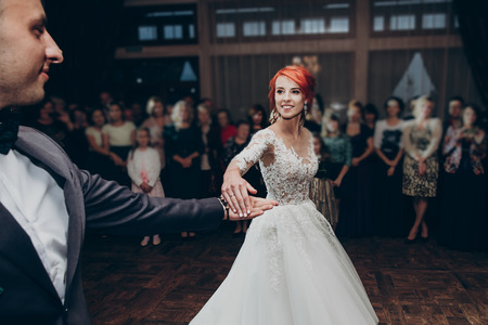 happy bride and stylish groom dancing at wedding reception. gorgeous wedding couple performing their first dance in restaurant. newlyweds, happy emotional moment. space for text Stock Photo