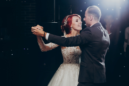 happy bride and stylish groom dancing at wedding reception. gorgeous wedding couple performing  first dance in restaurant. newlyweds,  emotional moment. space for text.