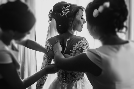 bridesmaids helping stylish happy bride fit in dress, back view at window, rustic wedding morning preparation in home. bridal getting ready. emotional moment. space for text. black white Stock Photo