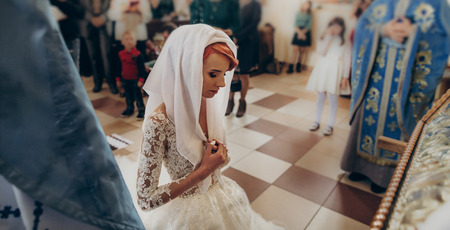 stylish bride praying during matrimony wedding ceremony in church. emotional moment, space for text. religion unity concept . spiritual couple Stock Photo