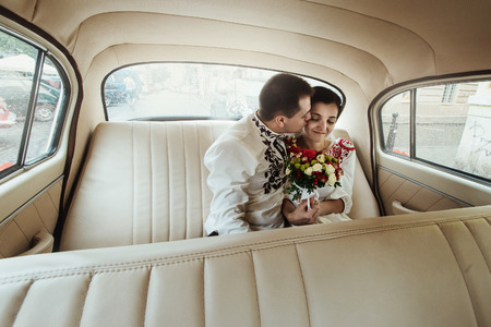 stylish groom kissing his lovely beautiful bride in retro car, gentle moment