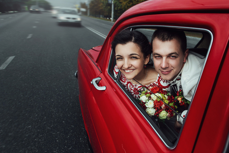 stylish bride and happy groom looking out of driving  retro car, having fun and kissing