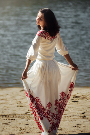 beautiful brunette stylish bride in unique embroidery dress in a sunny lake, concept of happiness