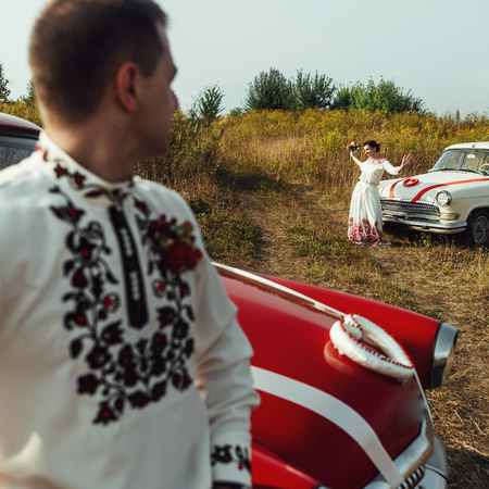 stylish bride and happy groom near  two retro cars on the background of nature