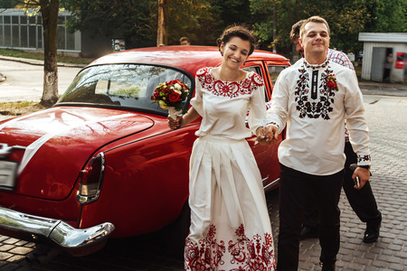 retro woman: stylish bride and happy groom near car on the background of restaurant