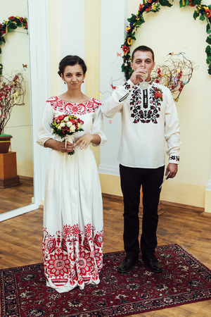 registry: stylish bride and groom, toasting and drinking champagne, traditional wedding ceremony