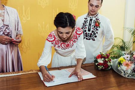 スタイリッシュな花嫁と花婿の公式の結婚式の登録に署名
