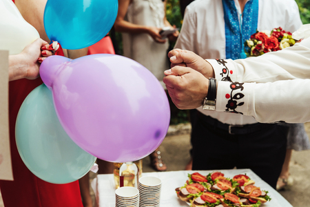 stylish groom having fun with pricking colorful balloons, wedding ceremony