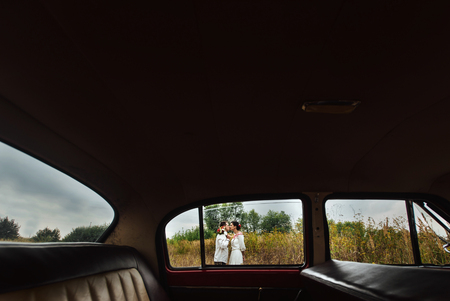 unusual view of stylish bride and happy groom through red retro car on the background of nature