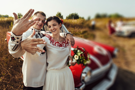 stylish bride and happy groom near car on the background of nature and friends bridesmaids