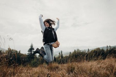 幸せな流行に敏感な旅行者は山の上にジャンプします。成功の感動的な瞬間。 テキストのためのスペースとの放浪癖と旅行のコンセプトです。スタ