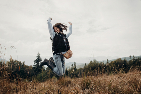 happy hipster traveler jumping on top of mountains. emotional moment of success.  wanderlust and travel concept with space for text. stylish woman hiking. atmospheric moment