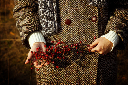 gorgeous stylish beautiful girl holding amazing red berries of hawthorn on a background of sunny autumn forest
