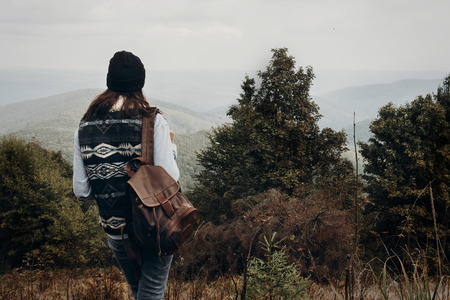 wanderlust and travel concept with space for text. hipster traveler looking at woods on top of mountains, amazing view. stylish woman hiking.  atmospheric moment