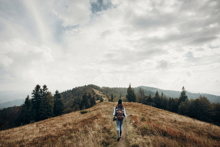hipster traveler with backpack walking on top of mountains. wanderlust and travel concept with space for text. stylish woman hiking. atmospheric epic moment Фото со стока