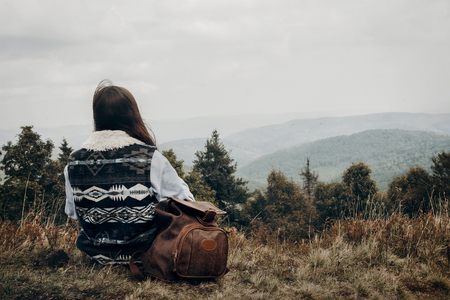 hipster traveler with backpack relaxing on top of mountains looking forward. wanderlust and travel concept with space for text. stylish woman hiking. atmospheric epic moment Фото со стока