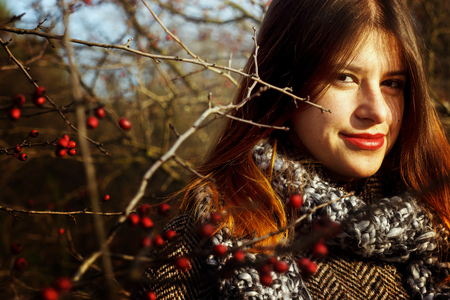 gorgeous stylish beautiful happy brunette girl and red berries of hawthorn on a background of sunny autumn forest Stock Photo