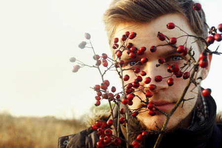 gorgeous stylish beautiful handsome blonde boy and red berries of hawthorn on a background of sunny autumn forest
