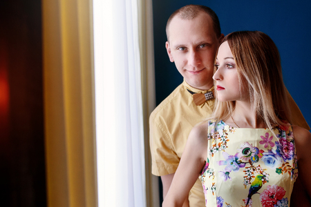 sexual intimacy: happy stylish couple hugging with tender at window light on background of luxury interior in studio, space for text