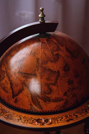 stylish pair of golden wedding ring on wooden old globe