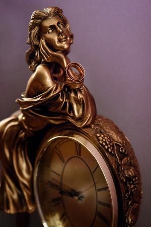 stijlvolle paar gouden trouwring op metalen gouden vrouw beeldje met klok, tijdconcept