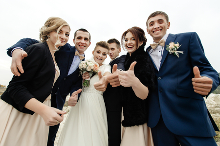 bride and groom with happy groomsmen and bridesmaids having fun and laughing at sandy lake, thumbs up Stock Photo - 76985160