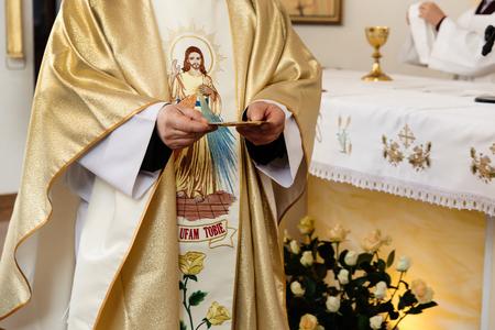 priester met gouden plaat voor de communie op de huwelijksceremonie in de kerk