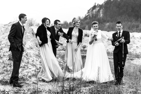 bride and groom with happy groomsmen and bridesmaids having fun and laughing and popping champagne, black and white
