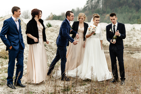 bride and groom with happy groomsmen and bridesmaids having fun and laughing and popping champagne, luxury wedding celebration