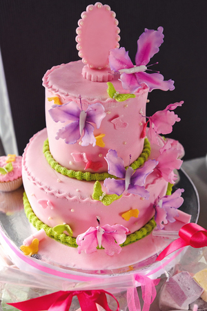 luxury delicious pink cake with colorful butterflies and candy bar at celebration, party in a restaurant
