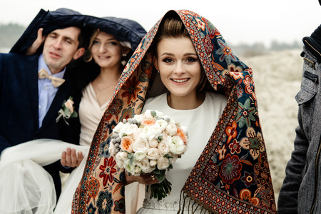 Glückliche Braut mit Blumenstrauß unter Schal mit Trauzeugen und Brautjungfern, die Spaß haben, draußen regnen, vergnügter Moment Standard-Bild - 76850284