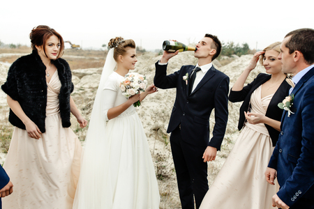 bride and groom with happy groomsmen and bridesmaids having fun and toasting with champagne, luxury wedding celebration, hilarious moment Stock Photo